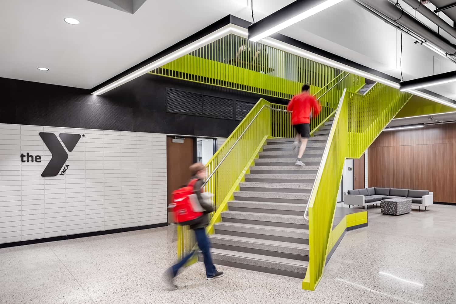 A bright green staircase invites gym-goers to take the stairs, and a seating alcove provides a quiet place for a post-workout rest.