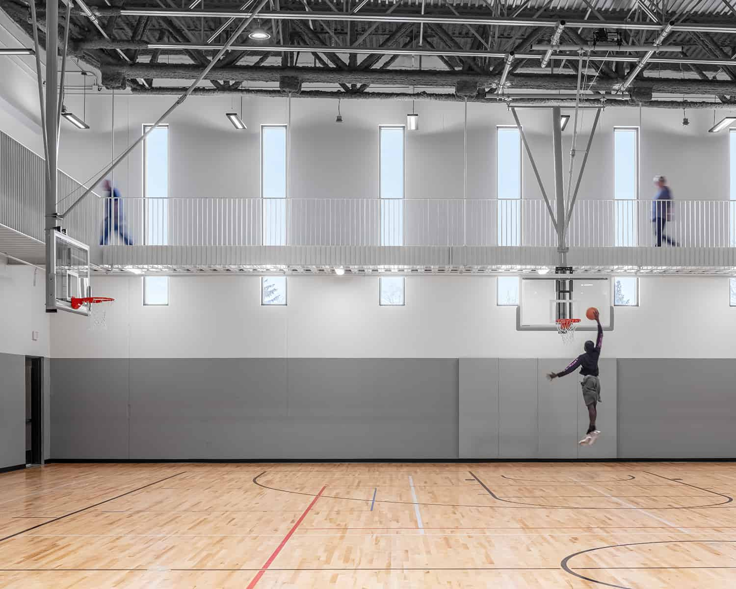 A basketball player and joggers utilize the open gym and track spaces simultaneously.