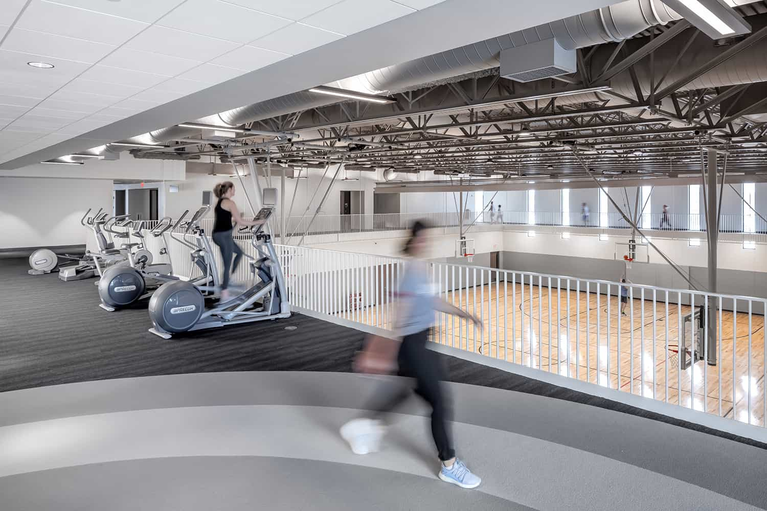 A jogger on the walking track passes an overlook into one of the gymnasiums.