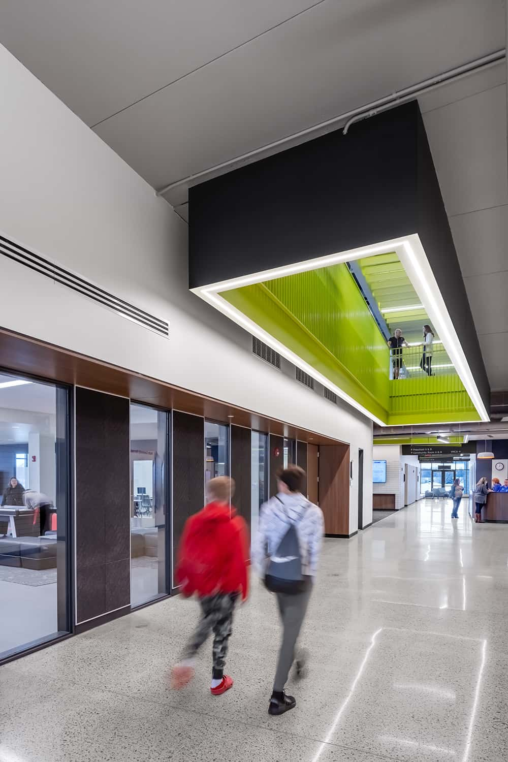 A main floor corridor leads to a welcome desk, community spaces, and a ceiling look-through into the upper level of the facility.