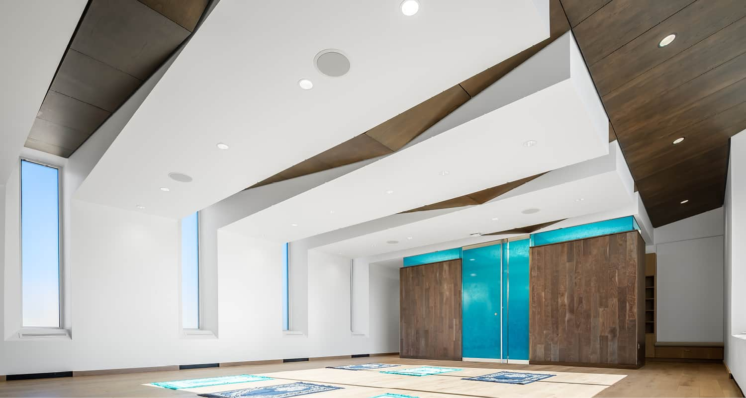 Full view of the multifaith center with worship mats on the floor and illuminated blue privacy glass at the entry.