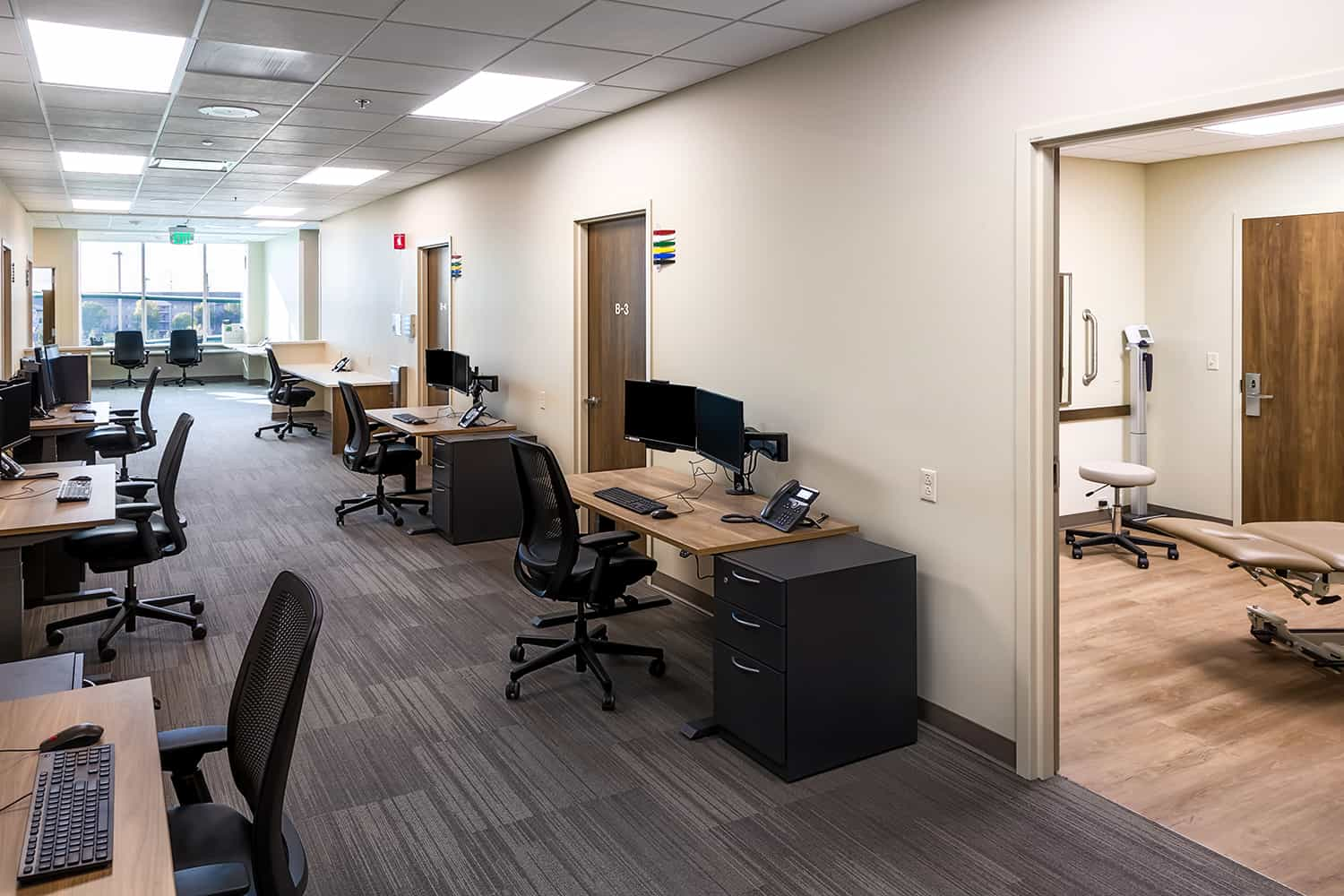 View of an interior staff core, with open workstations and double-loaded exam room access.