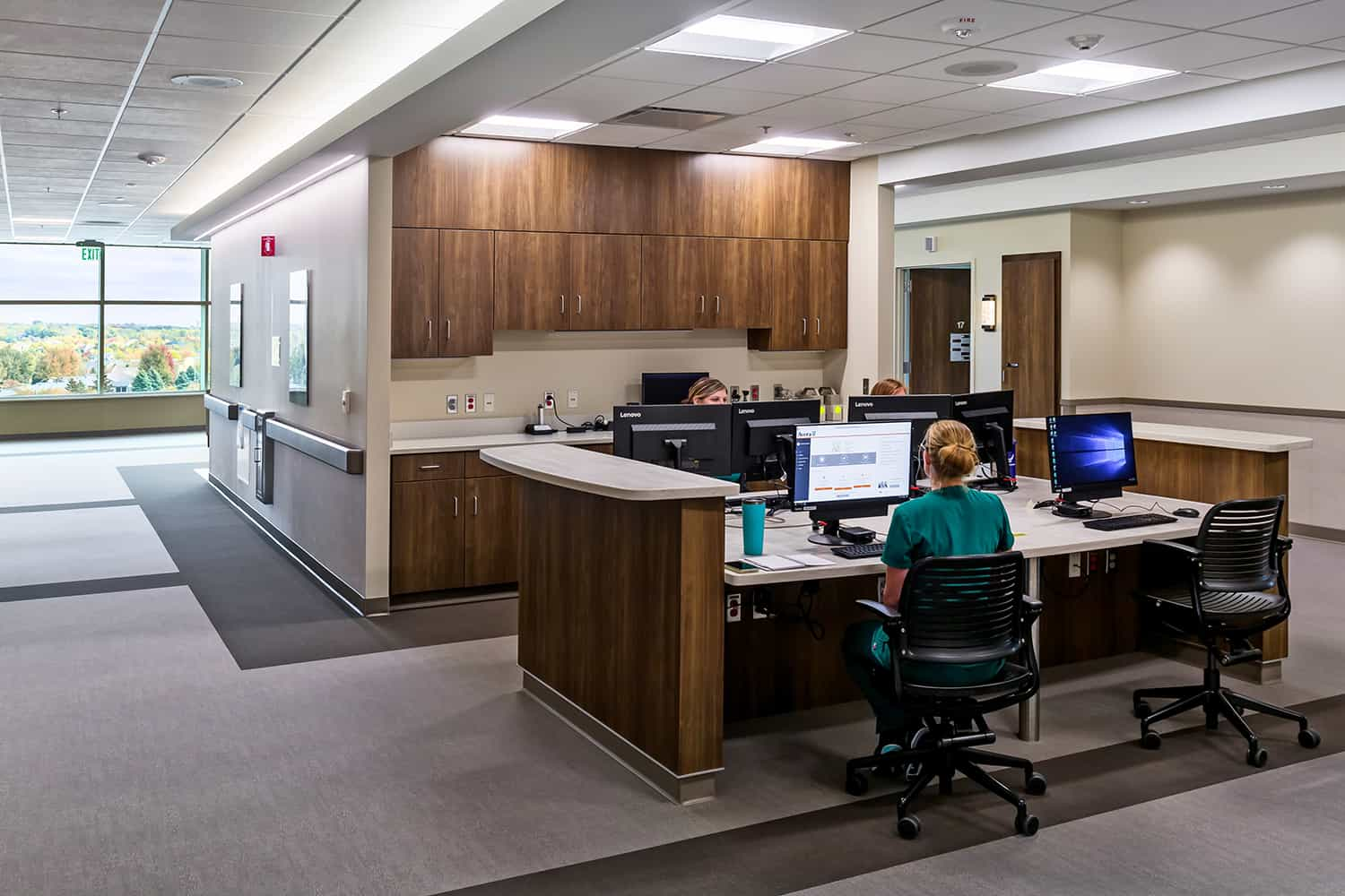 Open nurse station with wood casework and access to daylight and views.