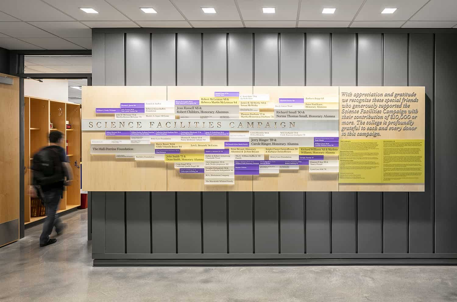 A wood panel donor wall mounted outside of a classroom that honors the Science Facilities Campaign.
