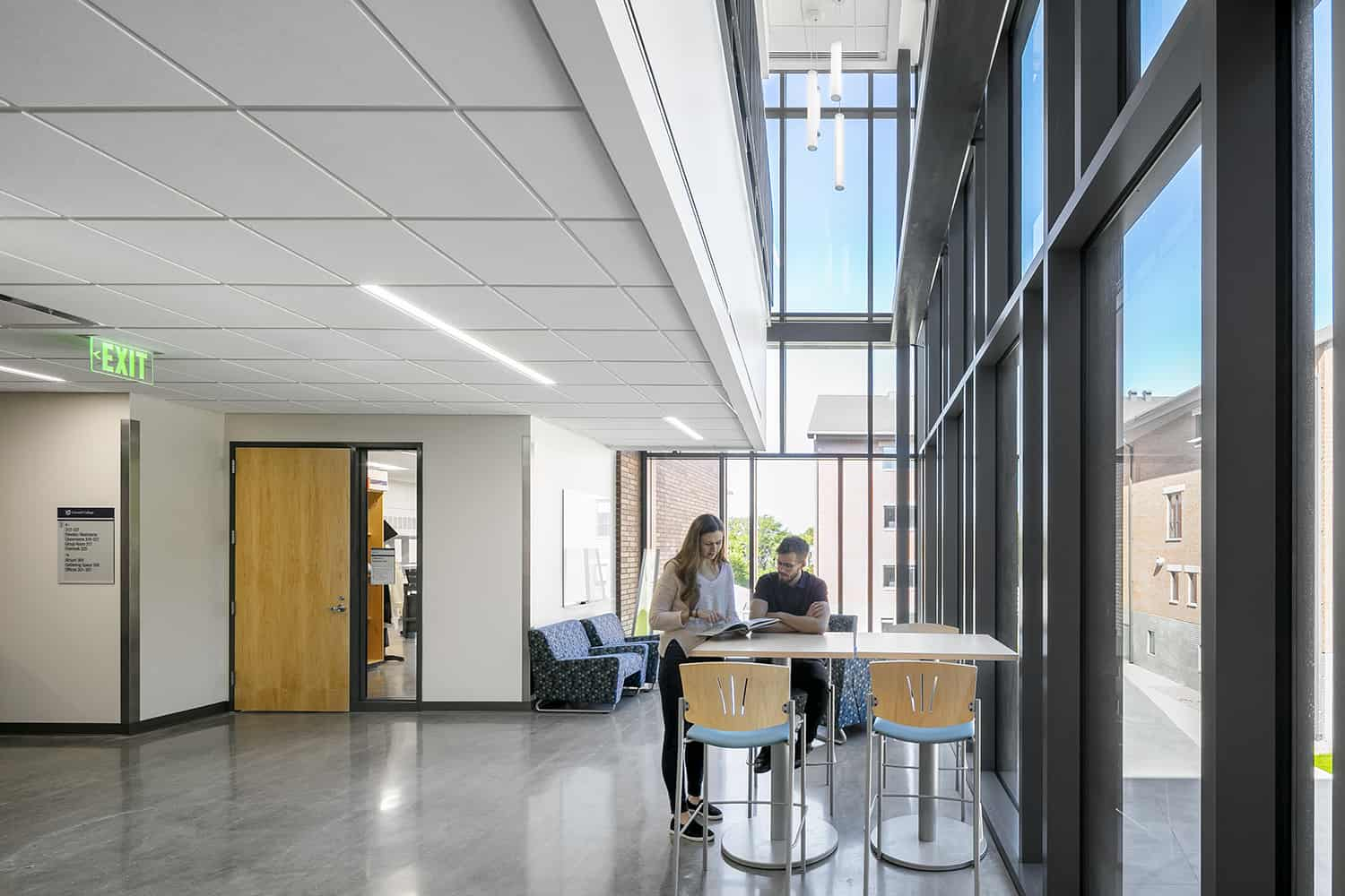 An open study area located in a classroom corridor, with two-story windows.