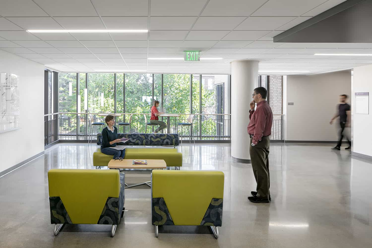 An open third floor lounge with brightly colored furniture and whiteboard workspace.