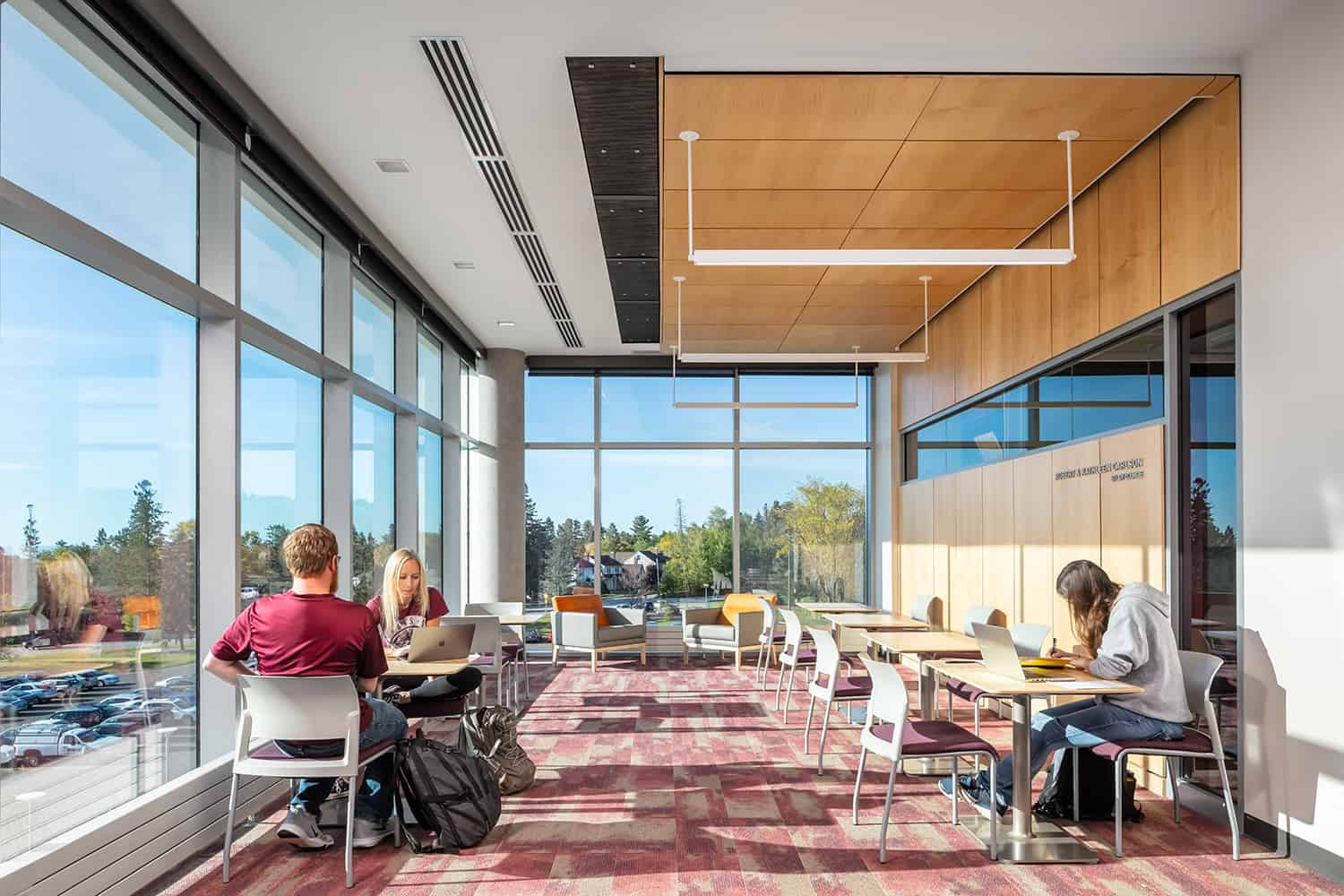 Students studying in a lounge space with floor to ceiling windows.
