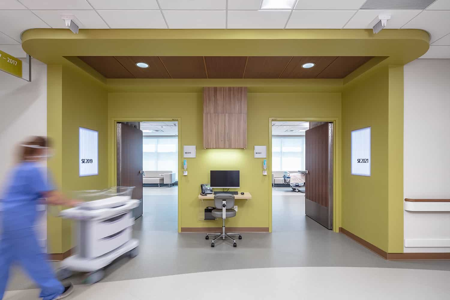 View from the corridor into two post op rooms with green entry wayfinding.