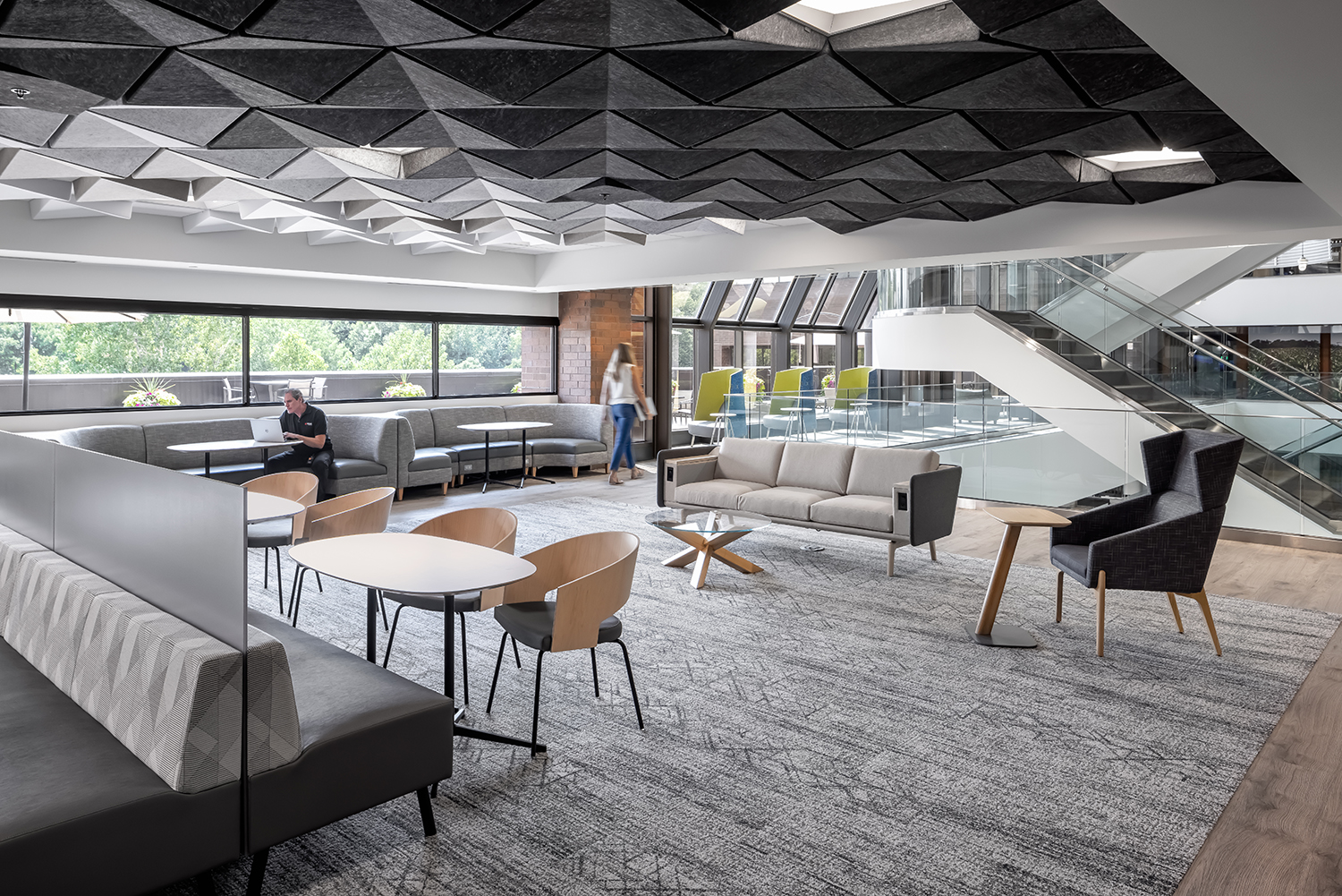 Various seating options in a CHS work cafe, and gray toned acoustical panels on the ceiling.