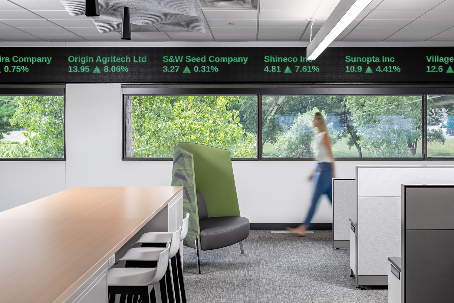 Office workspace with views to nature and trading floor digital panels at ceiling level.