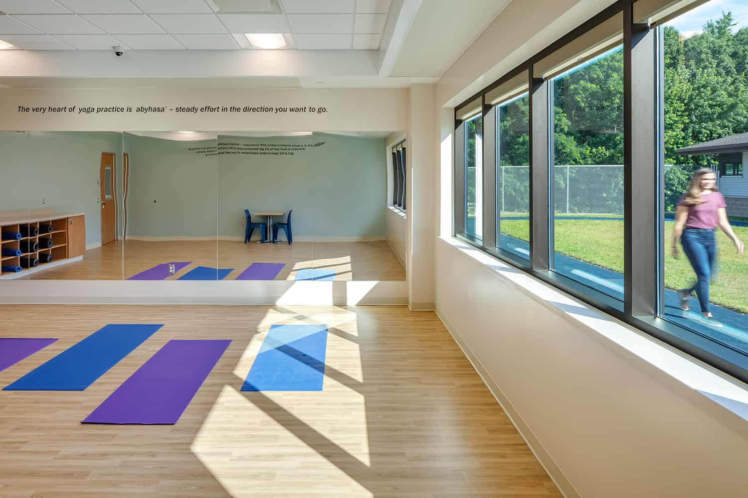 Meditation studio with expansive windows and view to a small walking track.
