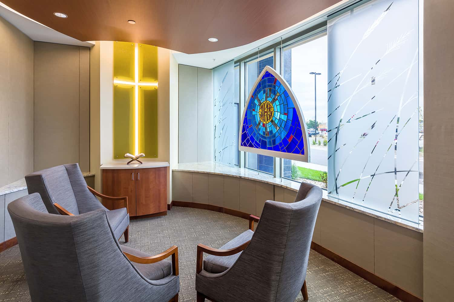 A calming meditation space with stained glass accent piece and lighted cross detail.