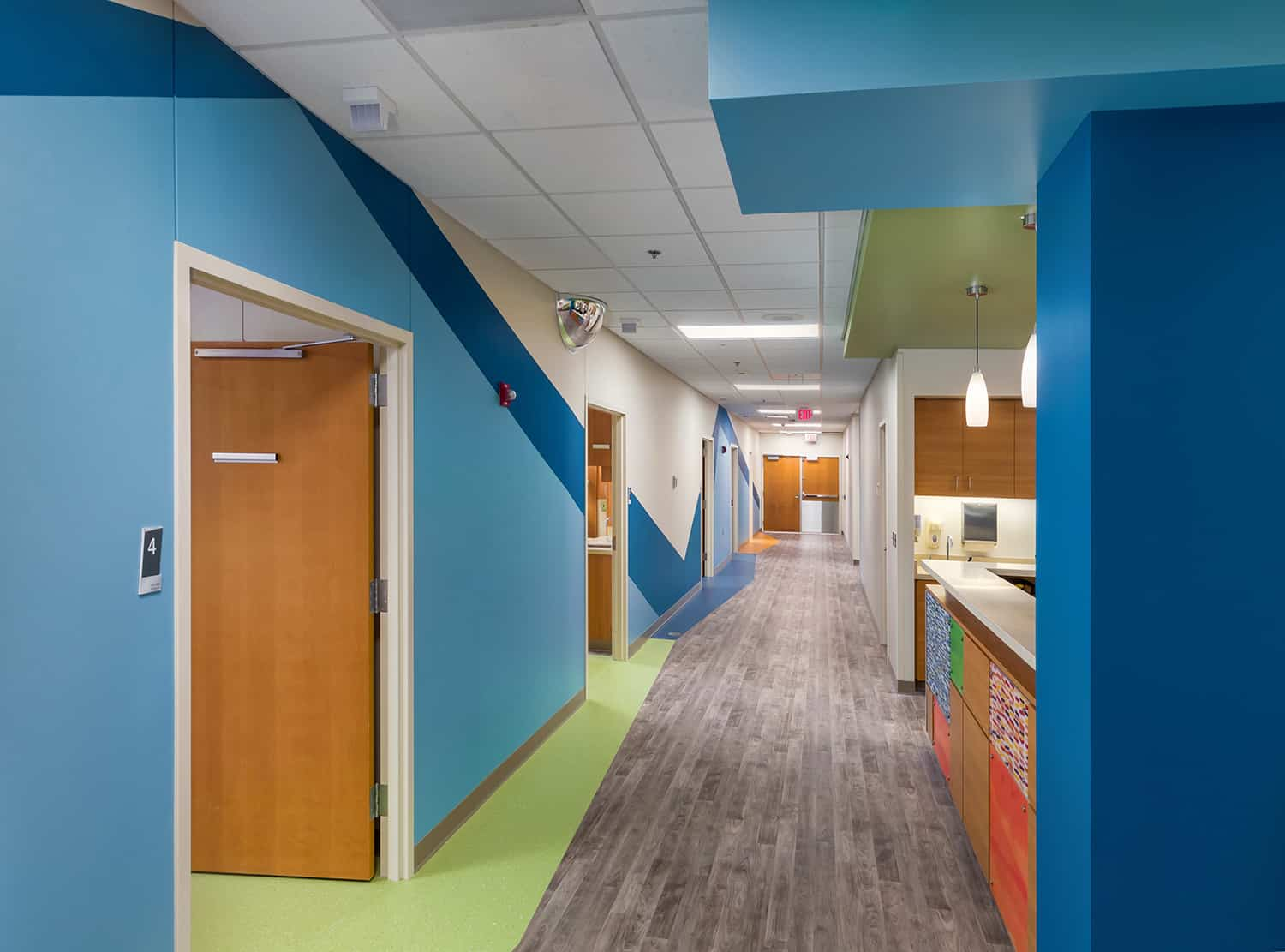 Pediatric unit corridor with a blue wall theme and view to the nurses station.