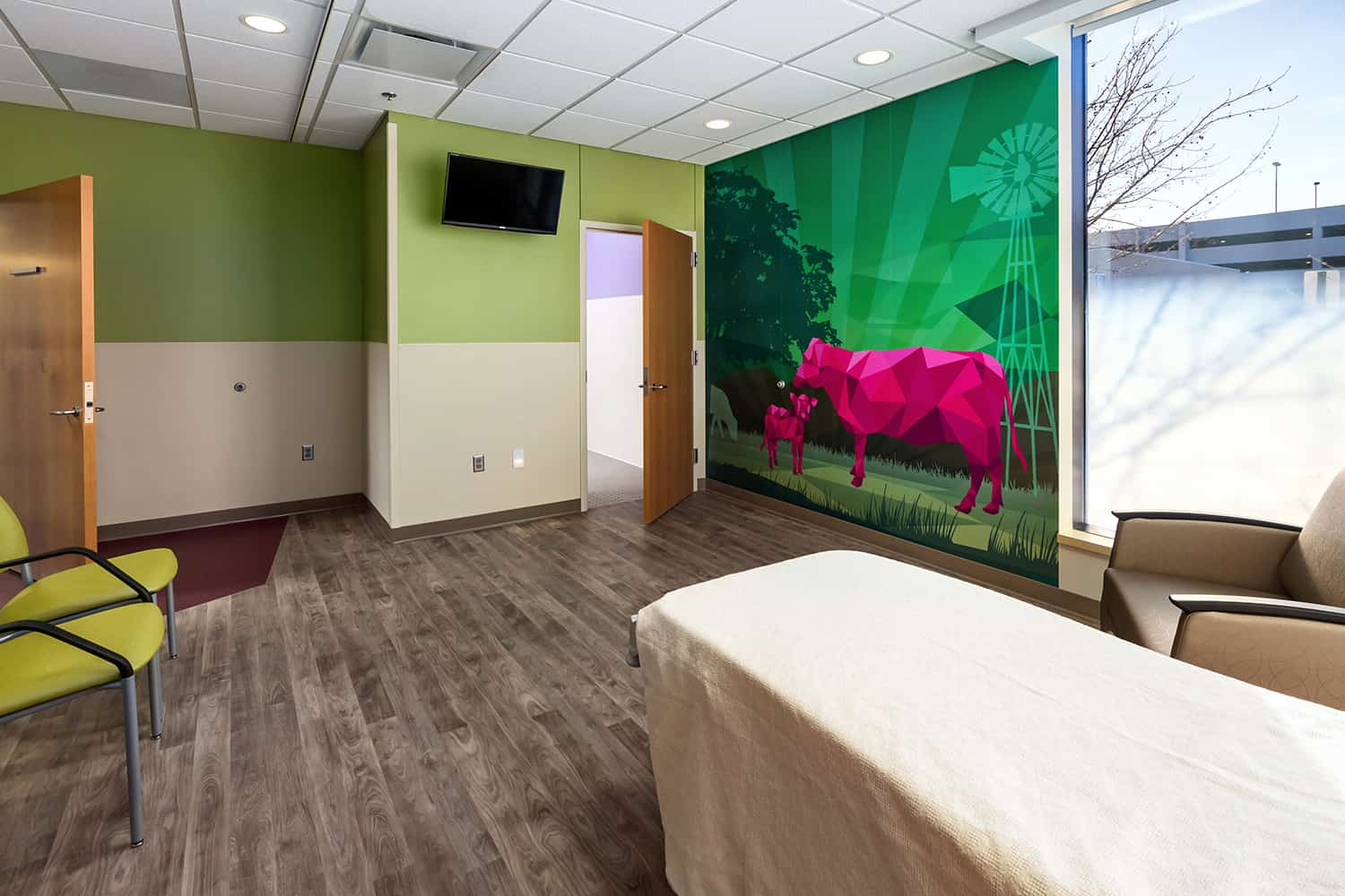 A patient room with a wall mural of cows.