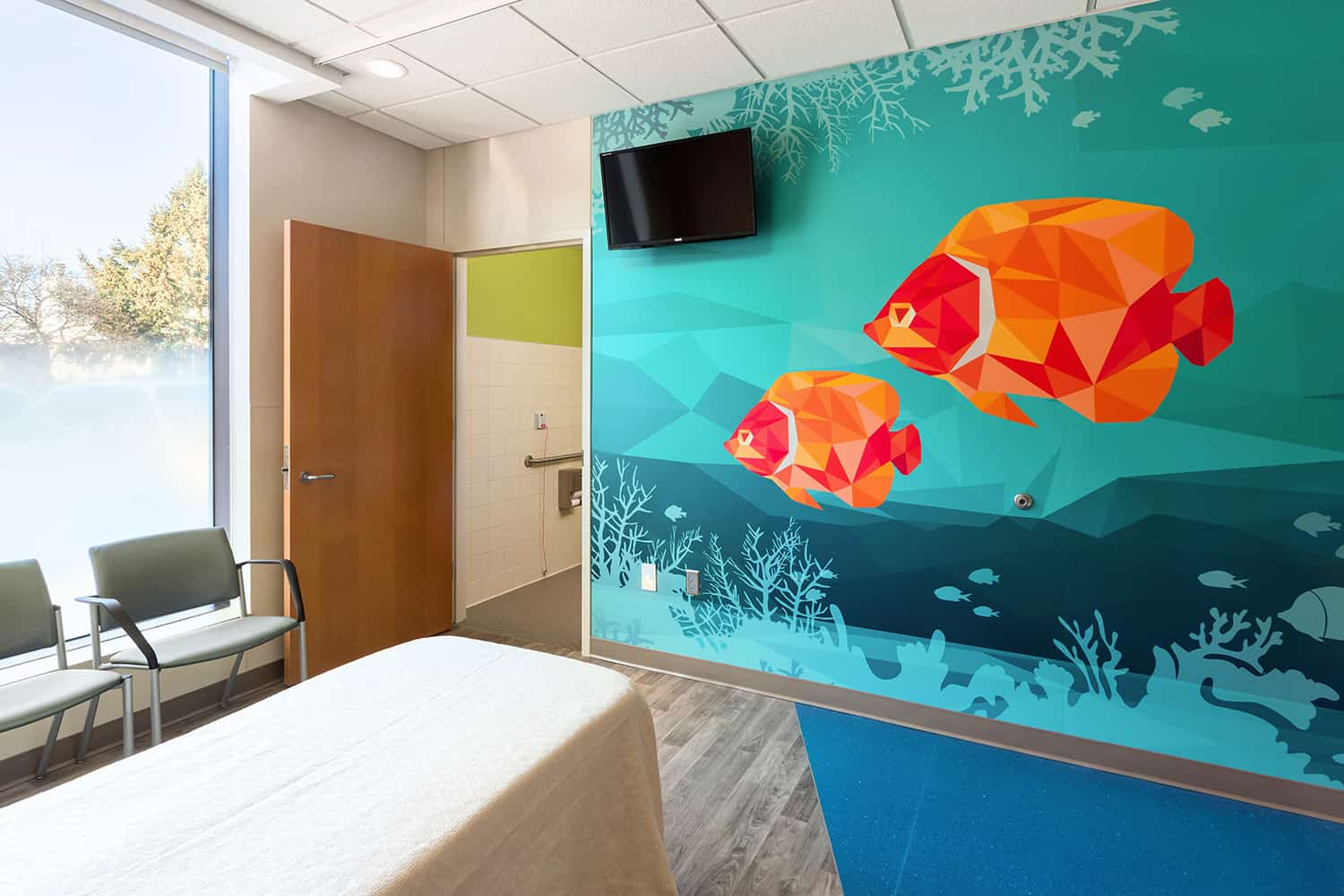 The footwall of a patient room with a wall mural of tropical fish.