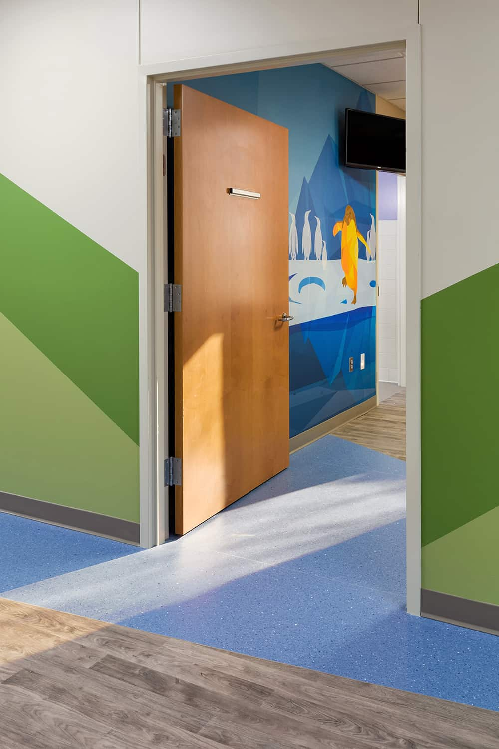 The door to a patient room with a view to a penguin wall mural.