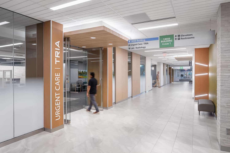 Interior corridor leading to Tria Urgent Care and additional services.
