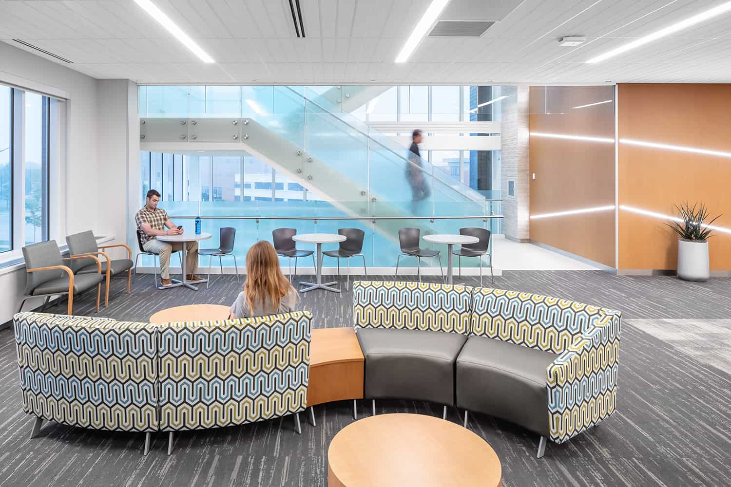 A waiting area with a variety of seating options and access to abundant daylight from the glass-enclosed stairwell.