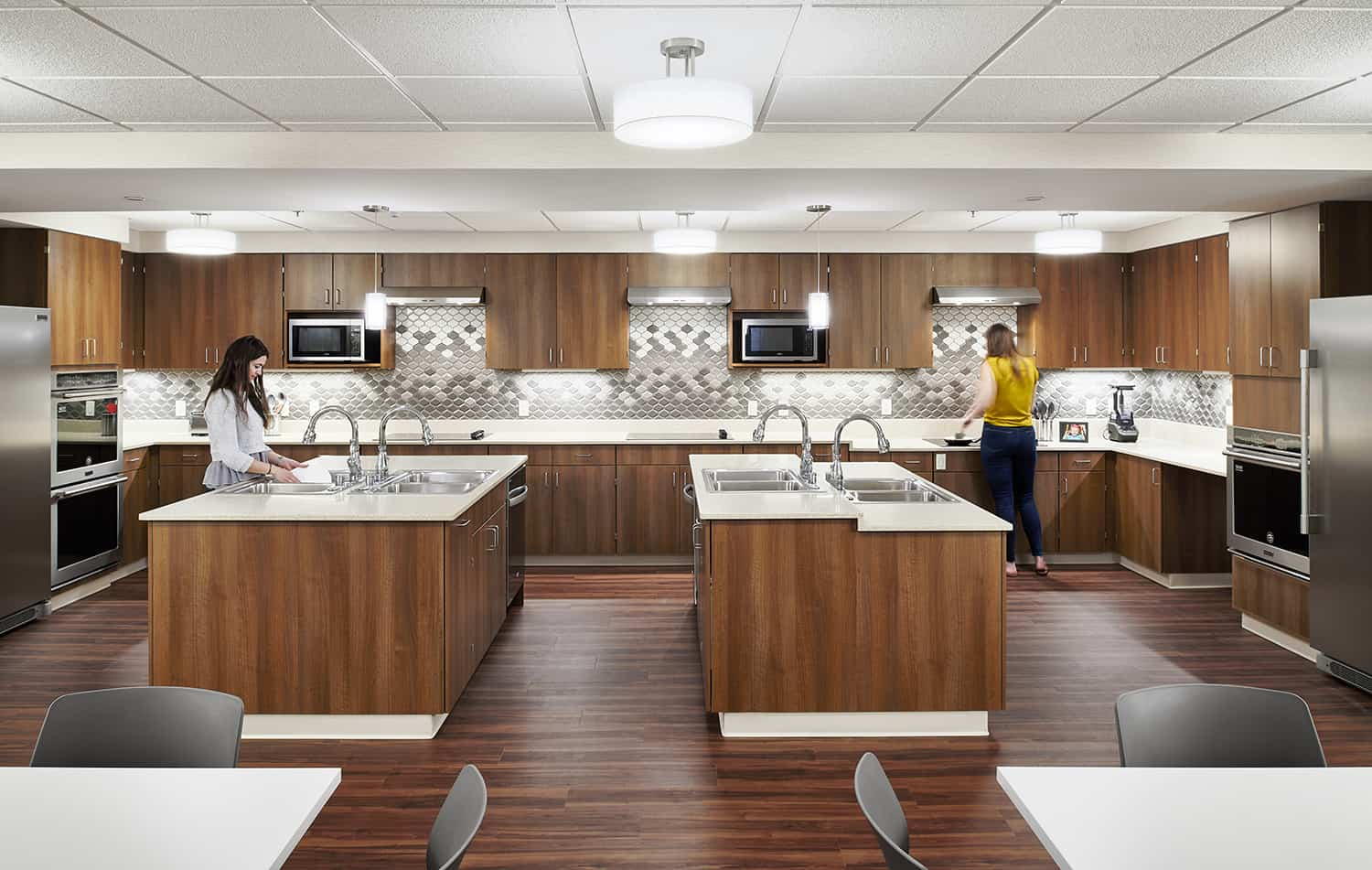 Focus on the shared kitchen area with four open food prep stations and warm wood paneling.