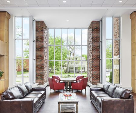 Shared open living space with floor to ceiling windows that let in daylight and views to the neighborhood.