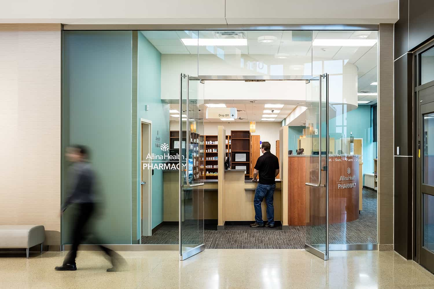 Entry to the Allina retail pharmacy with floor to ceiling glass and warm wood shelving.