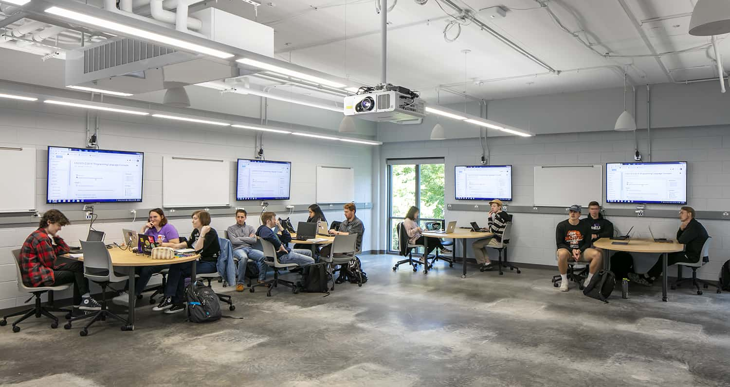 Students attending class in an active learning environment, complemented by mobile furniture, whiteboards, and large monitors.