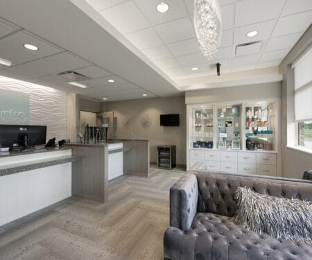 The luxurious waiting room for the clinic's spa, with glass chandelier and product displays.