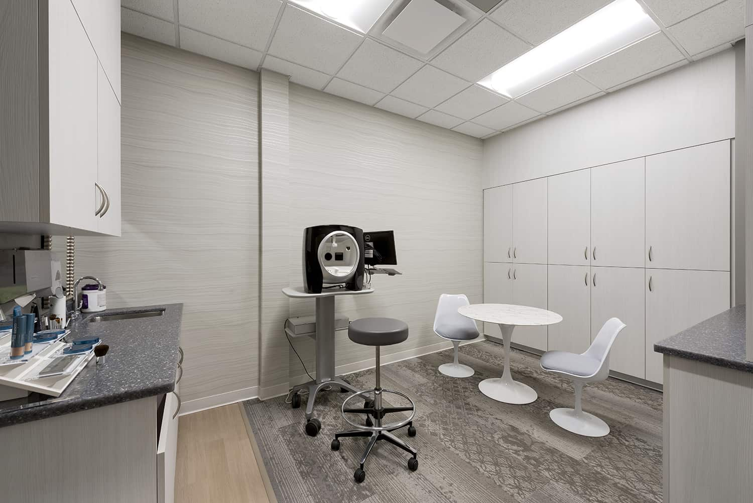 A dermatology procedure room with casework storage and in-room casual seating.
