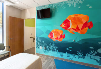 A pediatric patient room footwall with a graphic mural of tropical fish.
