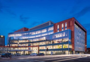 Exterior elevation of the Hennepin Healthcare Clinic & Specialty Center at dusk.