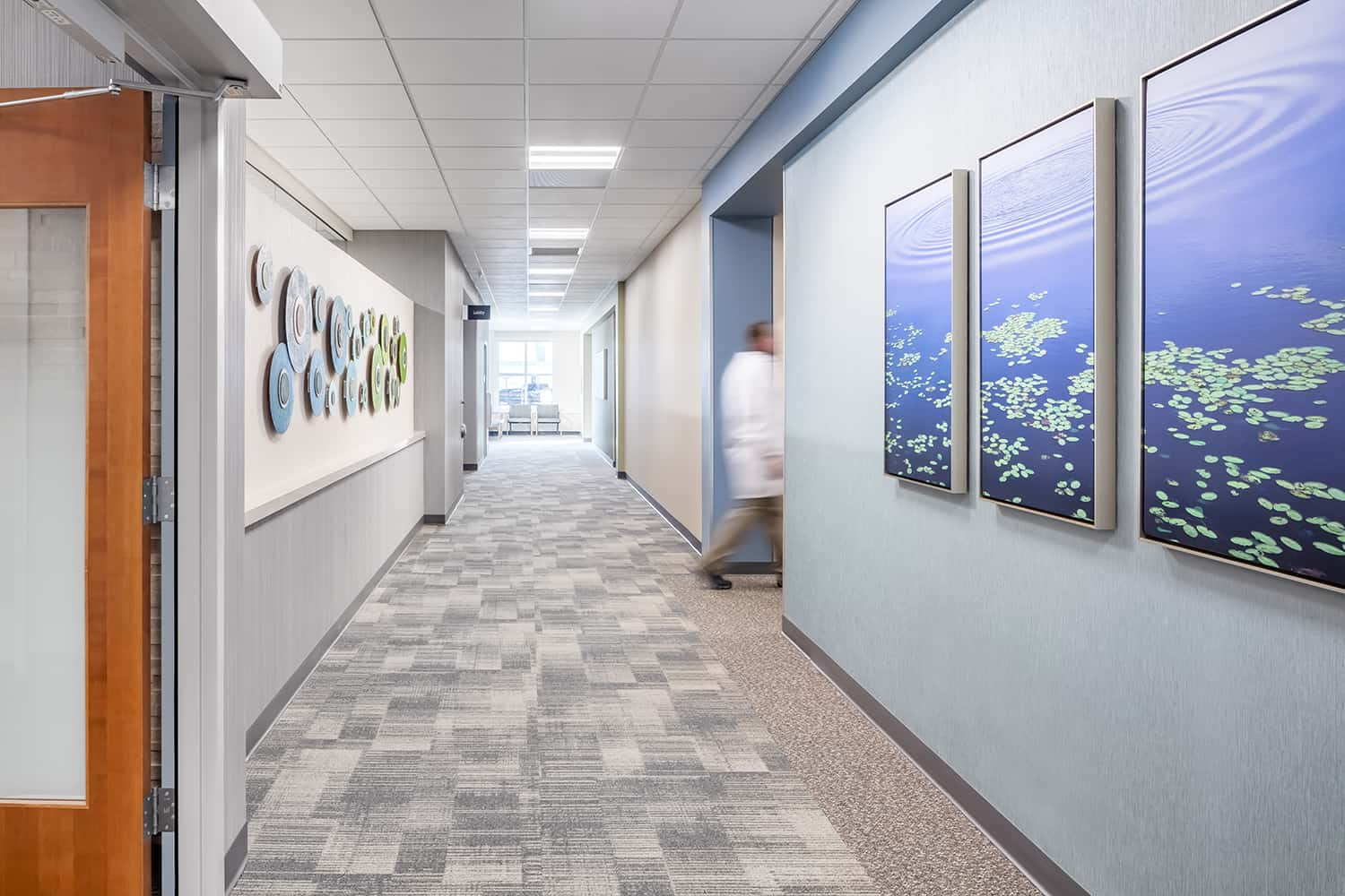 A doctor utilizes an interior corridor with nature-inspired artwork.