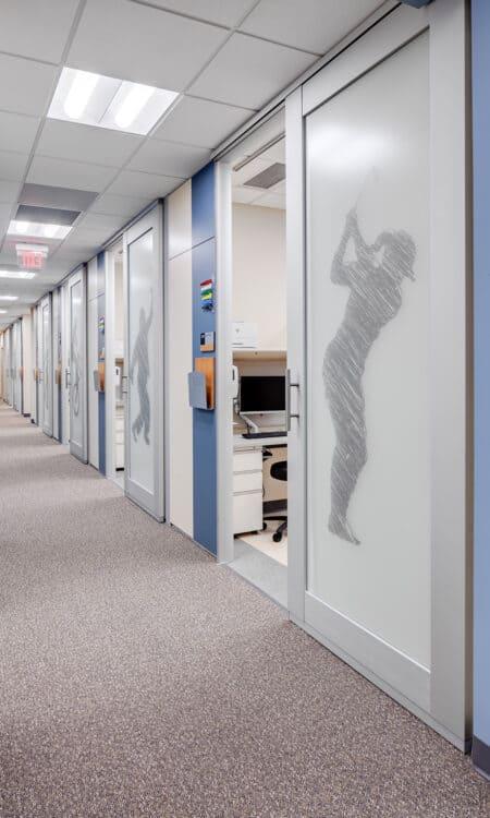 The orthopedic exam corridor with sports graphic film coverings on sliding exam room doors.