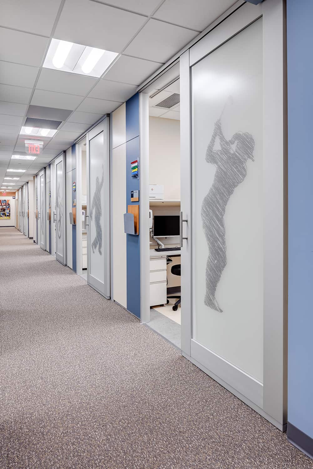 The orthopedic exam corridor with sports graphic film coverings on sliding exam room doors.