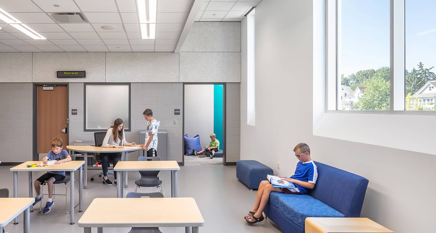 Students in a classroom with a variety of study spaces.