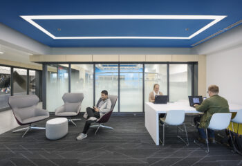 A study space in Shepherd Robotics Lab with an illuminated blue ceiling and seating options.