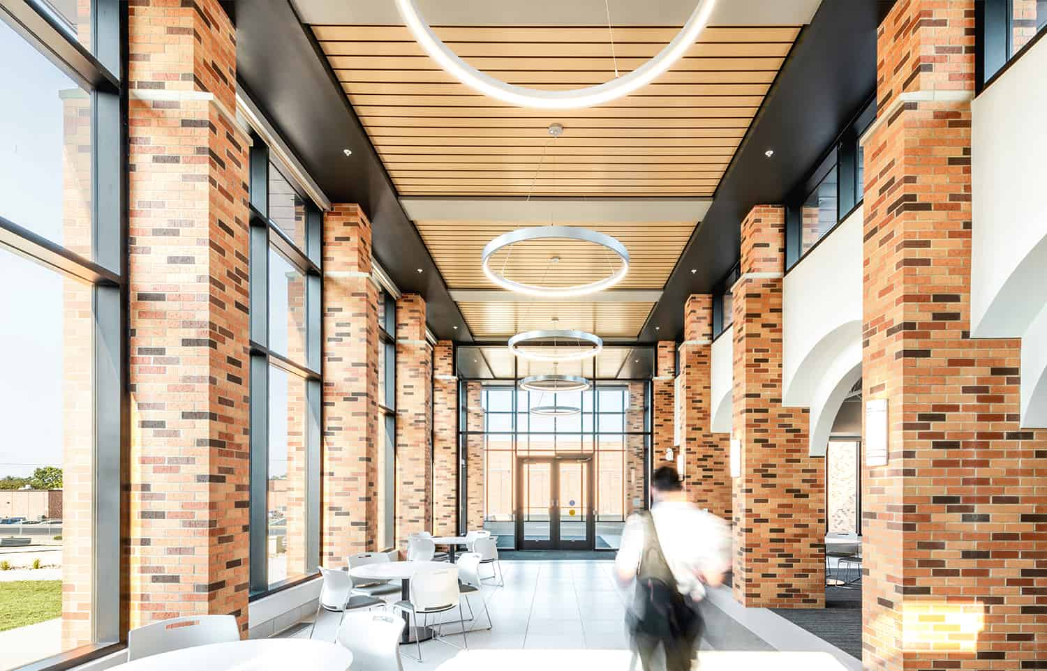 Interior corridor in the entry to the Healthcare Center of Learning, surrounded by exposed brick, wood paneling, feature circular lighting, and open seating.