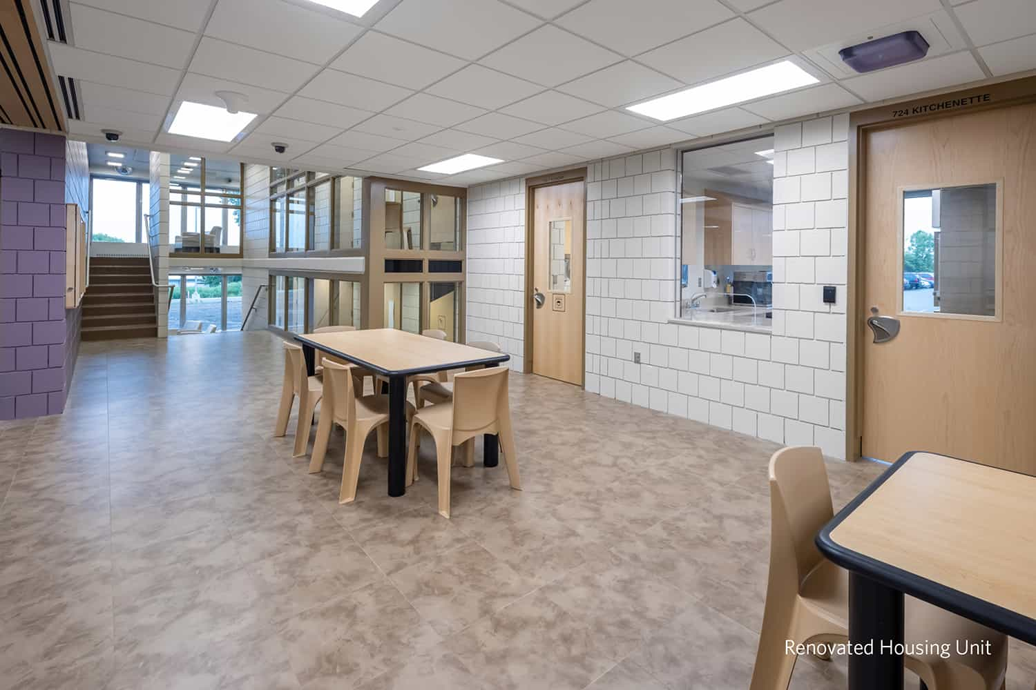 Dining and flexible seating in a renovated housing unit.