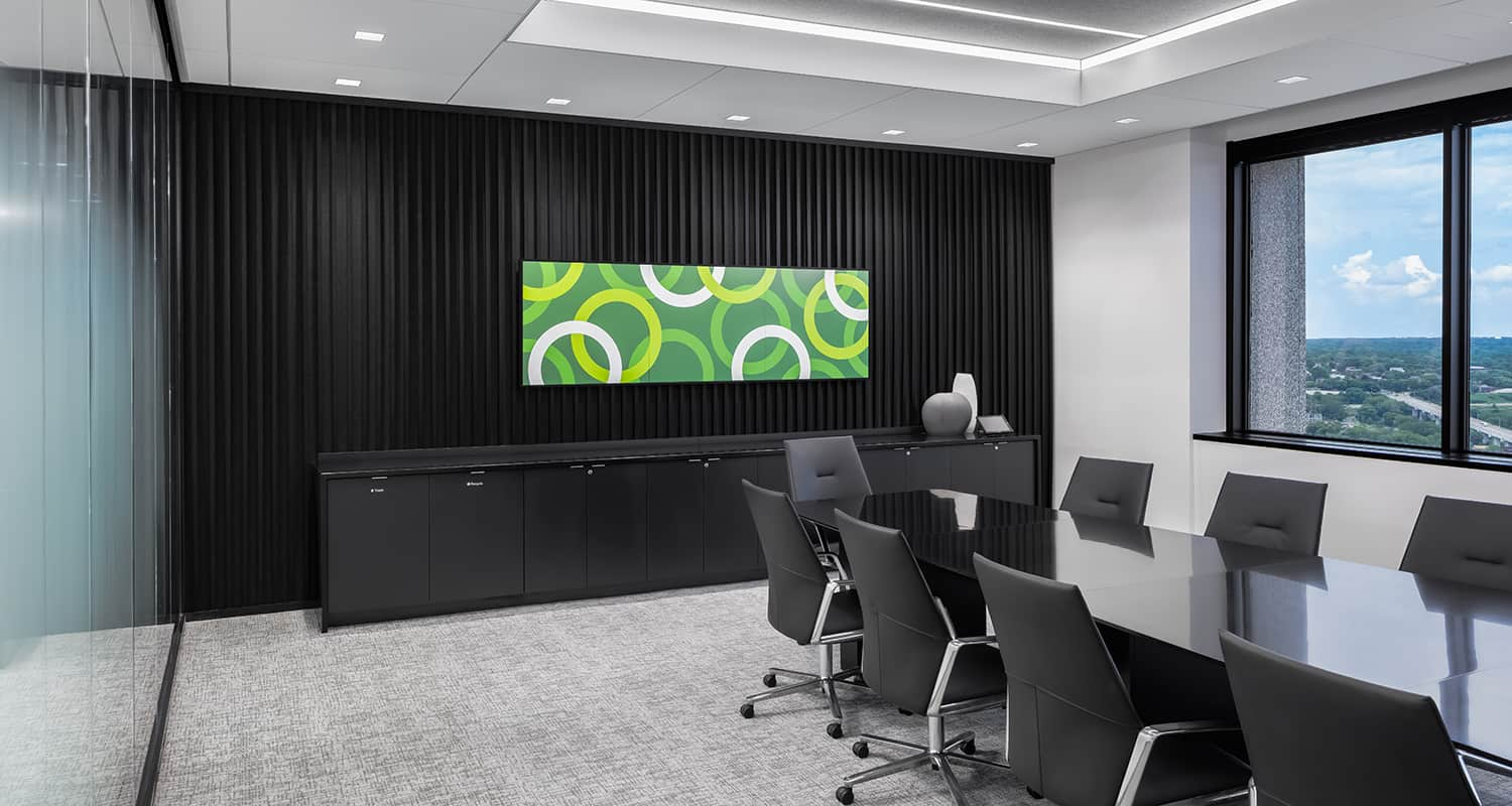 A meeting room with striking furniture, an accent wall that puts the focus on the display screen, and custom privacy glass.