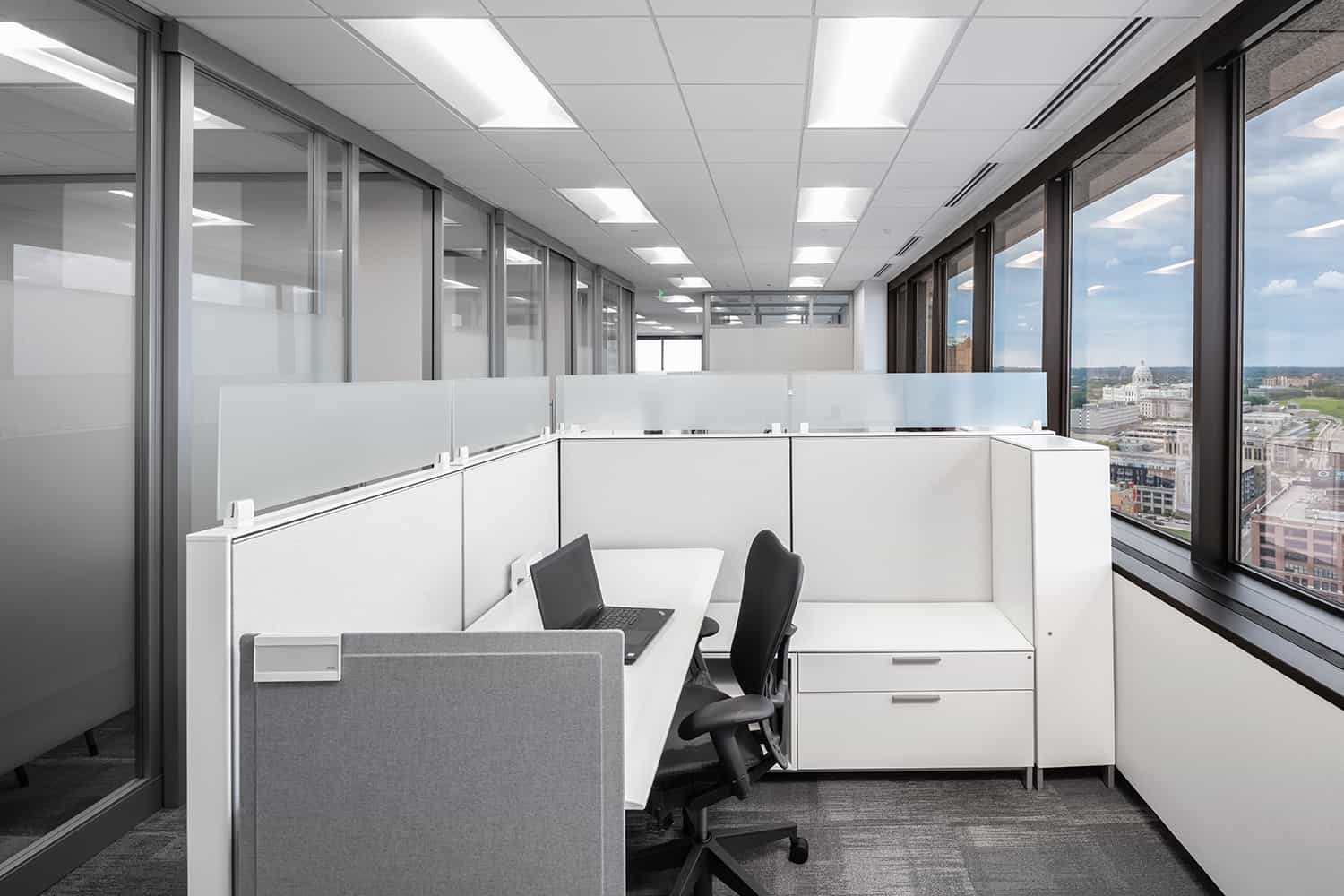 An office cubicle with flexible desk settings and access to daylight.