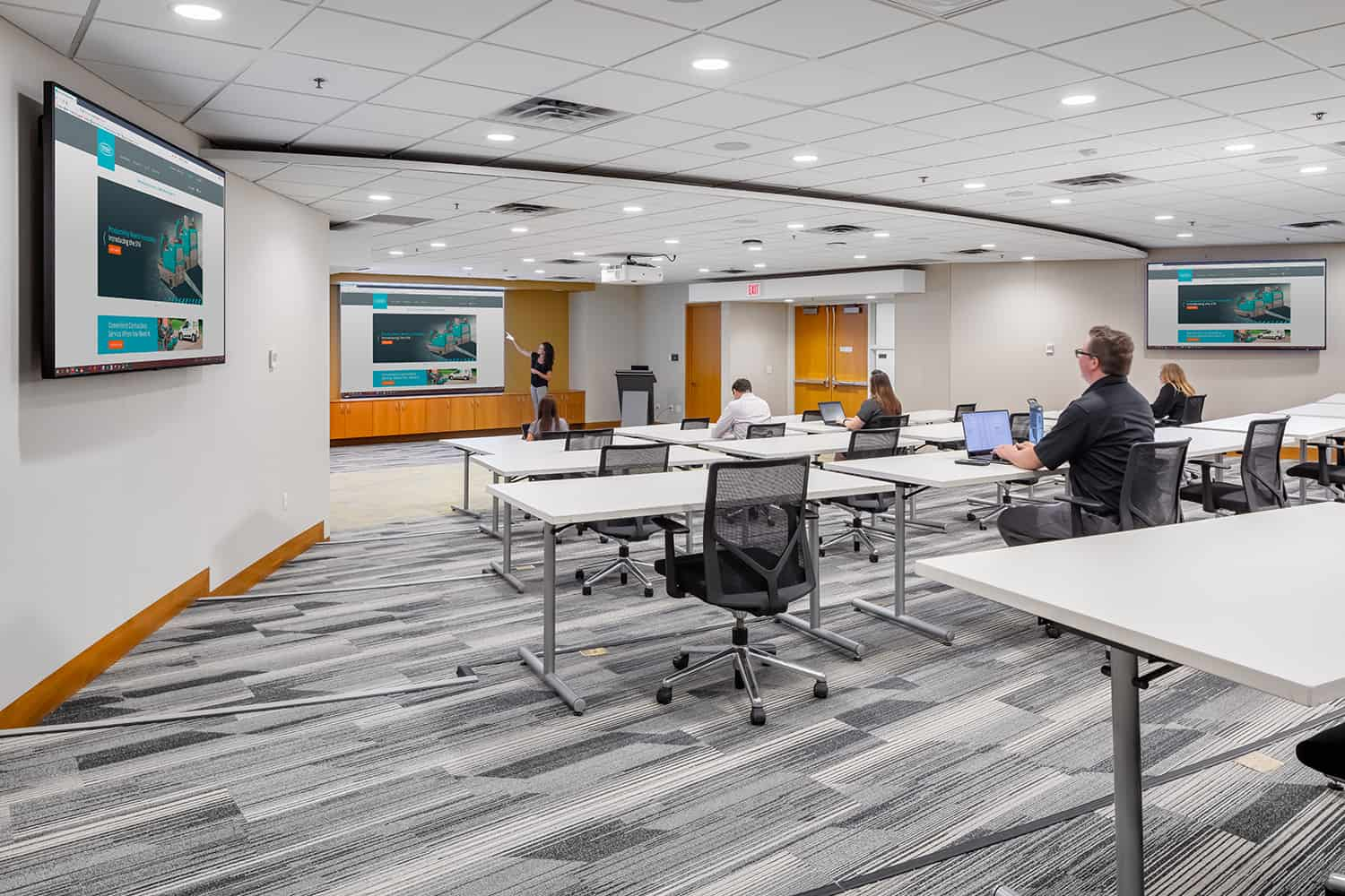 A large conference room with multiple monitors throughout the room.