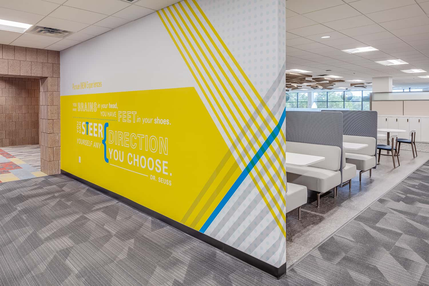 Environmental graphic wall with yellow branding and inspiring message.