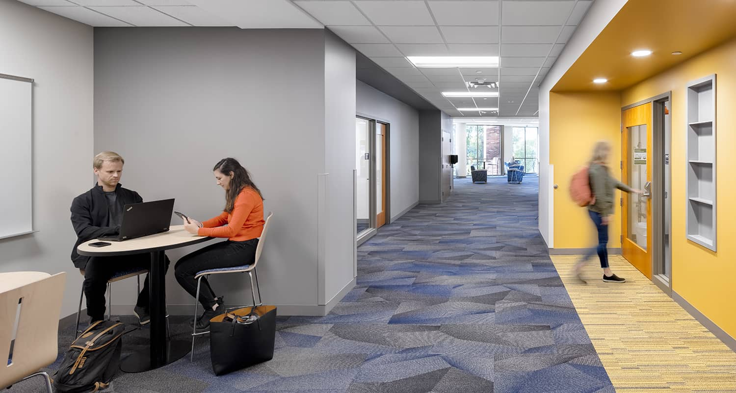 A typical corridor with touchdown space for students to gather and lab entry emphasized by bright colors and built-in storage.
