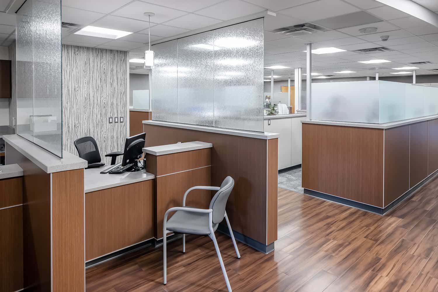 A check-in desk at a nurse station with privacy shields and warm wood tones.