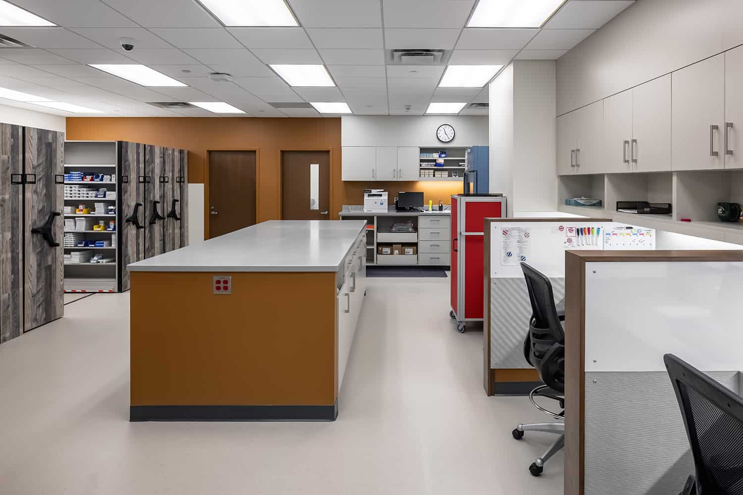 The new pharmacy space with rolling storage shelves and staff workstations.