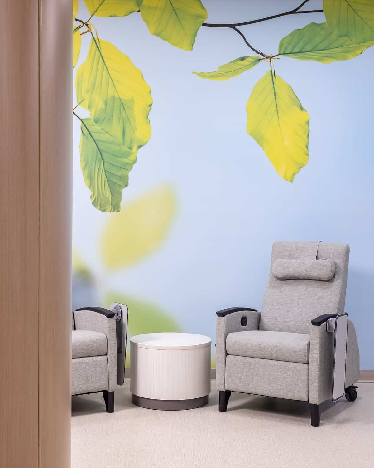 Quiet seating area with comfortable recliner and soothing wall mural depicting leaves.