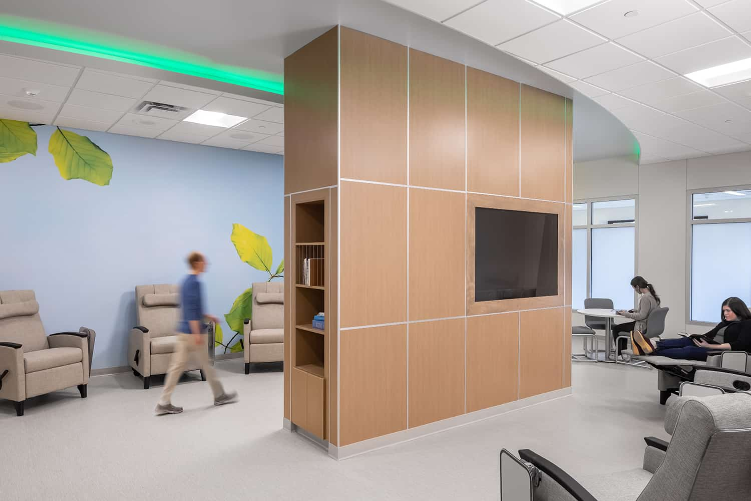 Group therapy space with technology and reading resources and comfortable furniture.