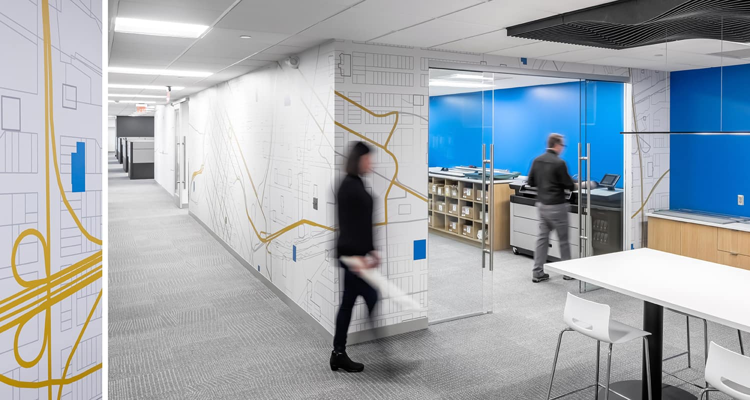 An environmental wall graphic highlighting a corridor that leads to a shared print room.
