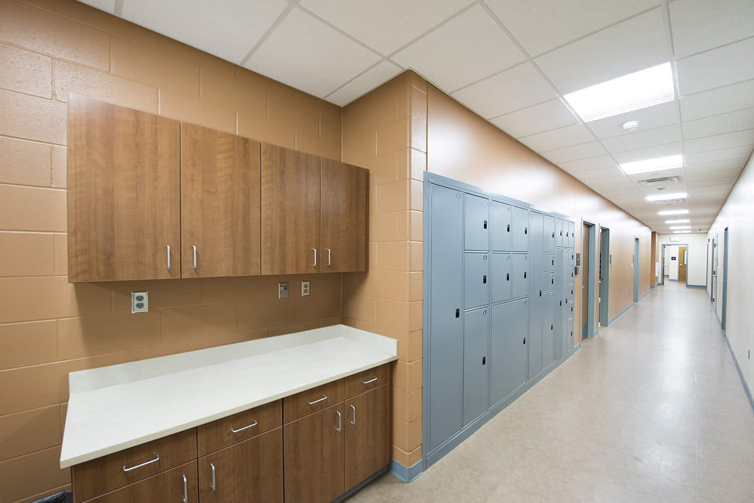 Staff corridor with touchdown workstation and evidence storage lockers.