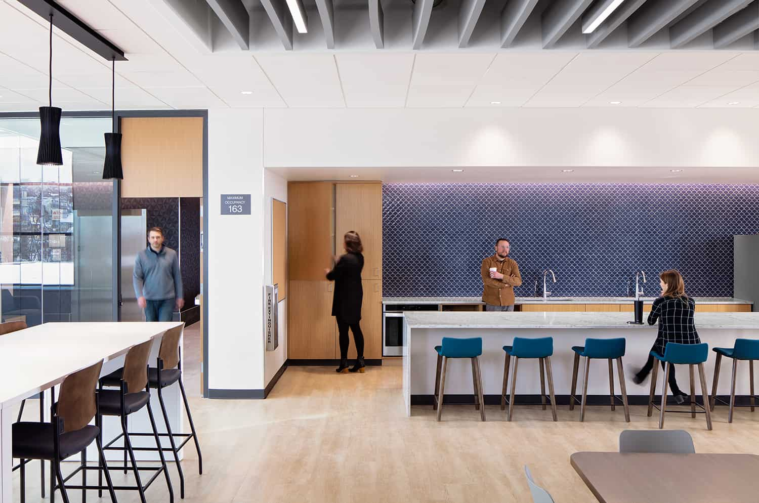 The work cafe with drop-in seating and a blue backsplash.