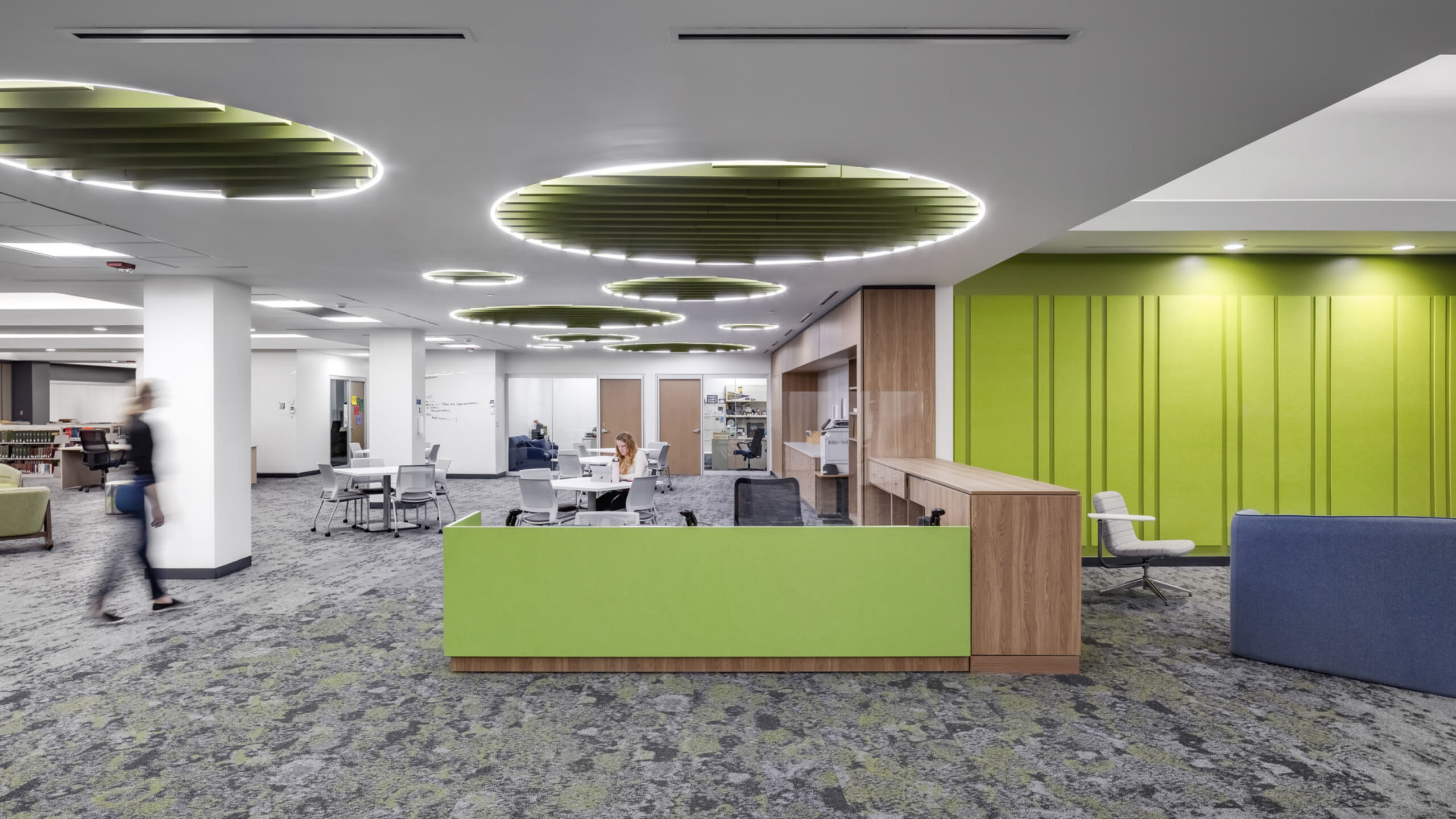 The library tutoring desk with bright green wayfinding elements.
